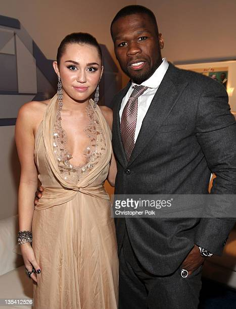 Actress/singer Miley Cyrus and rapper 50 Cent backstage at the American Giving Awards presented by Chase held at the Dorothy Chandler Pavilion on...
