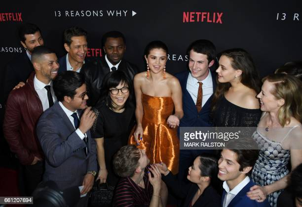 Actress/singer Selena Gomez is surrounded by cast members as they arrive for the premiere Of Netflix's '13 Reasons Why' at Paramount Pictures Studio...