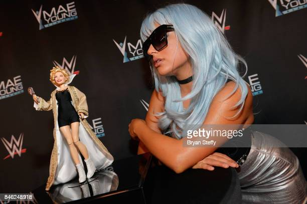 Actress/YouTube personality Inanna Sarkis poses with the Mae Young one of a kind fashion doll created by Matel and designed by Linda Jane on the red...