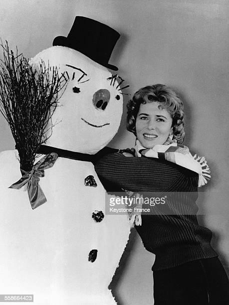 L'actrice allemande Cornell Borchers posant devant un bonhomme de neige en Allemagne le 20 décembre 1956