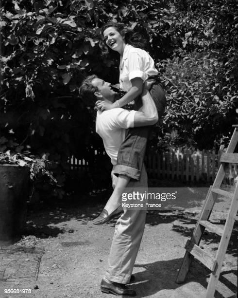 Actrice américaine Jane Russell dans les bras de son mari le joueur de football américain Bob Waterfield dans leur jardin, circa 1950 aux Etats-Unis.