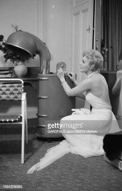 L'actrice américaine Kim NOVAK est la vedette inconnue du Festival de Cannes 1956 plan de profil de l'actrice en robe du soir à dosnu accroupi devant...