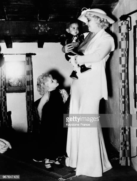 L'actrice américaine Mae West pendant sa visite à la Foire de San Diego tient dans ses bras l'enfant d'une femme naine avec qui elle s'entretient...