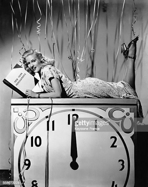 L'actrice américaine Marilyn Maxwell allongée sur une horloge relit ses bonnes résolutions du Nouvel An le 25 novembre 1946 à New York City NY