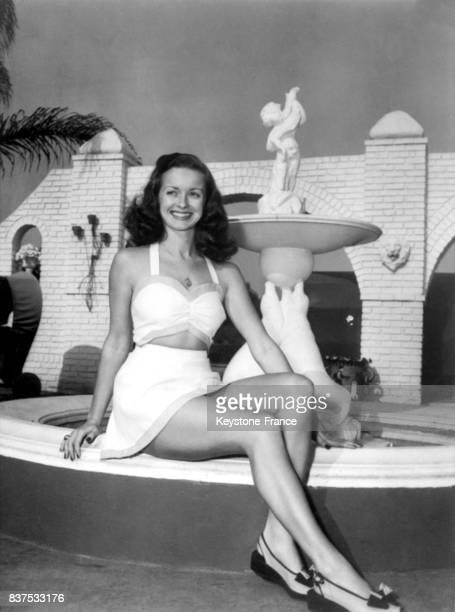 Actrice américaine Noel Neill posant assise devant une fontaine, aux Etats-Unis en 1946.