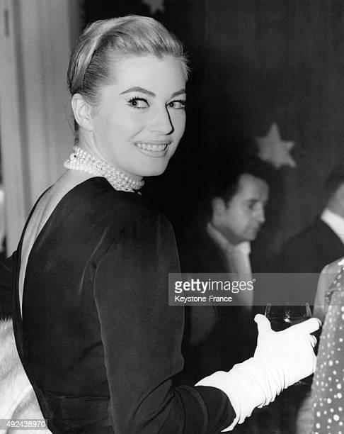 L'actrice Anita Ekberg vetue d'une robe noire decolletee dans le dos et portant des gants blancs au dejeuner des femmes de la Convention...