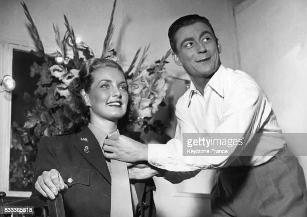 L'actrice britannique Patricia Roc en uniforme de lieutenant et son partenaire Fraçois Périer dans les studios François 1er à Paris France en 1948