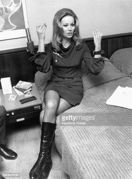 L'actrice Claudine Auger venue présenter son nouveau film 'Les Héros ne meurent jamais' est interviewée assise sur le lit de la chambre d'hôtel à...