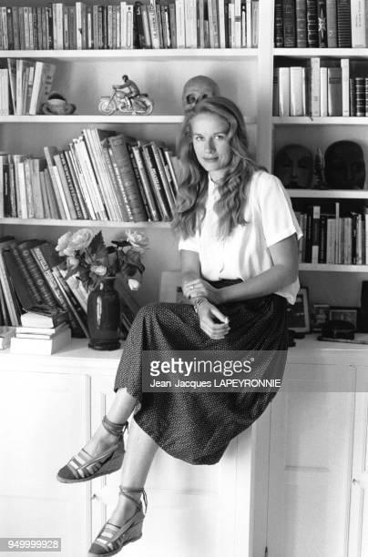 Actrice Dominique Sanda assise sur le rebord de sa bibliothèque dans sa ferme de Houdan, France, en juin 1978.