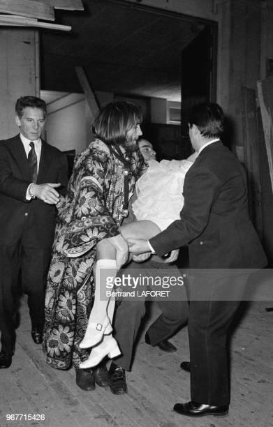 L'actrice Elisabeth Wiener évanouie lors d'une émission de télévison est évacuée par Gérard Depardieu et JeanPierre Aumont le 27 avril 1970 à Paris...
