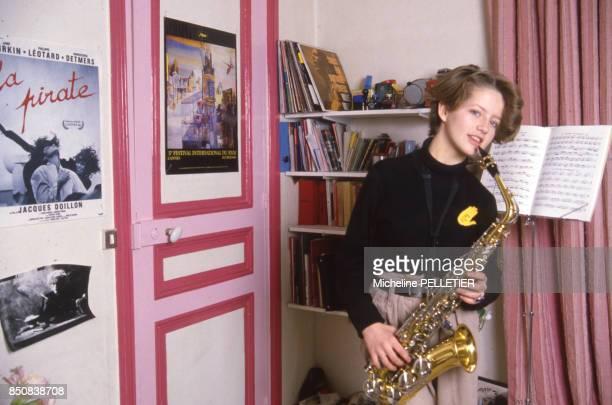 L'actrice française Laure Marsac joue du saxophone chez elle à Paris le 13 mars 1985 France
