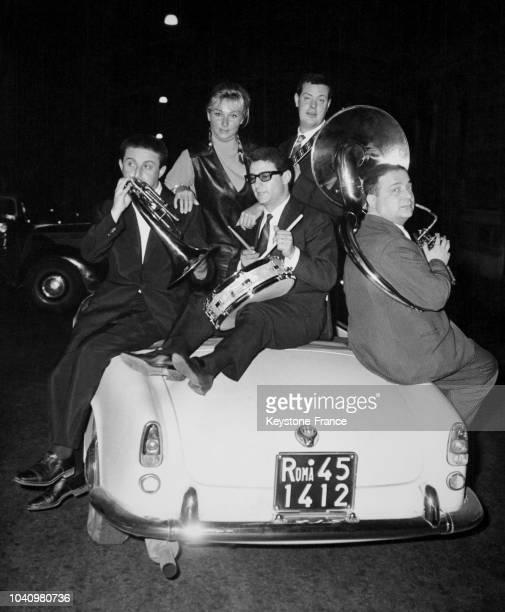 L'actrice italienne Annie Gorassini à bord d'une voiture entourée d'un orchestre de jazz dans les rues de Rome Italie en juin 1961