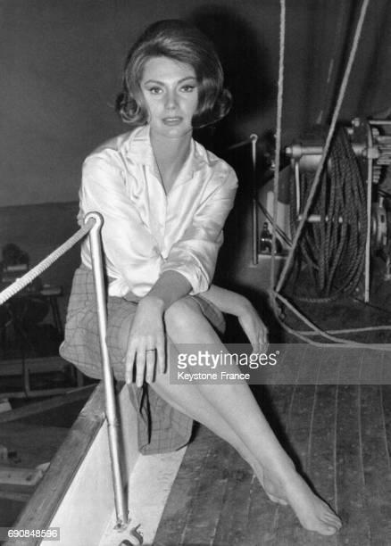 L'actrice italienne Sylva Koscina assise sur le pont d'un bateau en chemisier blanc jupe à carreaux et pieds nus