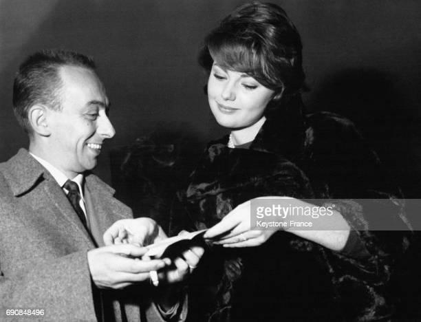 L'actrice italienne Sylva Koscina dans un beau manteau de fourrure regarde le papier que lui présente un homme souriant