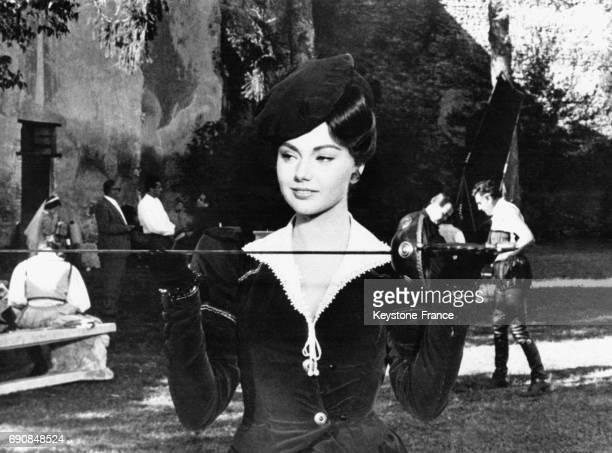 L'actrice italienne Sylva Koscina présente son épée tandis que Stewart Granger se prépare en arrièreplan pour le film 'Le Mercenaire' réalisé par...