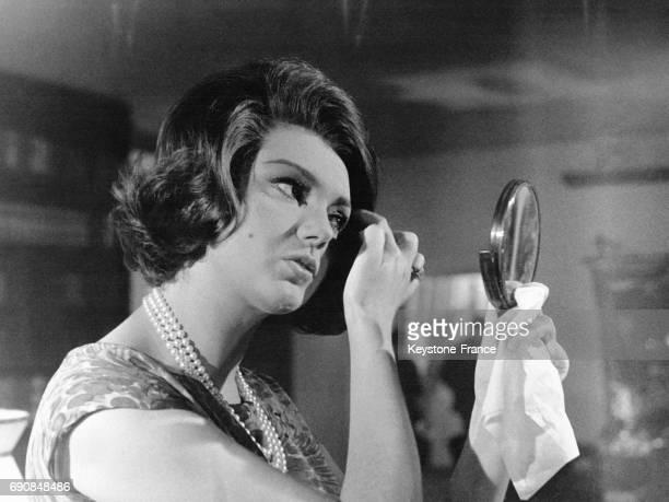 L'actrice italienne Sylva Koscina se recoiffe en tenant un miroir avec un mouchoir à la main