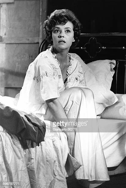 L'actrice Jeanne Moreau en chemise de nuit assise sur un lit durant une scène du film de Bunuel en novembre 1963 en France