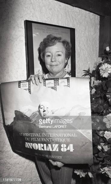 L'actrice Patricia Hitchcock fille de Alfred Hitchcock tenant l'affiche du 12e festival international du film fantastique d'Avoriaz janvier 1984