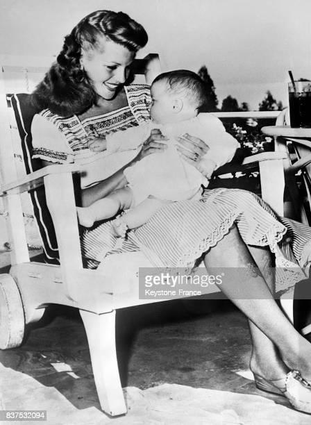L'actrice Rita Hayworth regarde admirative sa fille Rebecca Welles assise sur ses genoux aux EtatsUnis en 1946