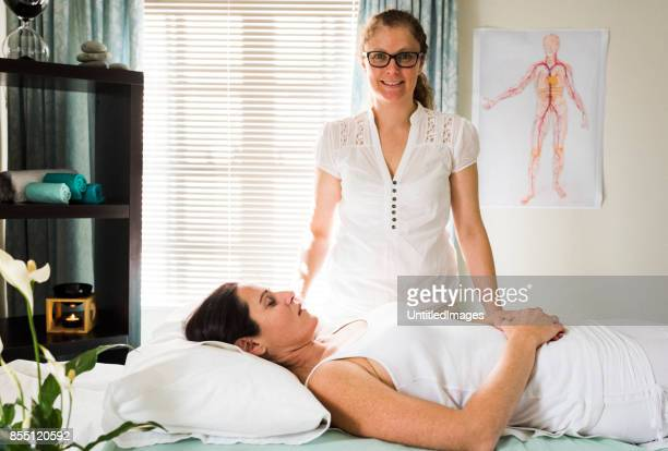 acupuncture therapist standing with patient in foreground - acupuncture needle stock pictures, royalty-free photos & images
