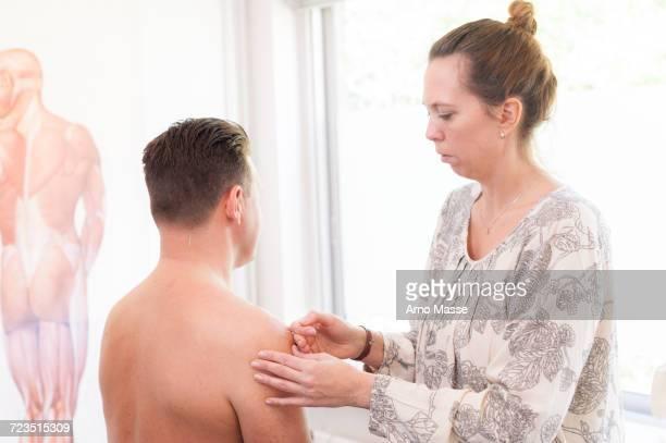 acupuncturist inserting acupuncture needles into patients skin - druckpunkt stock-fotos und bilder