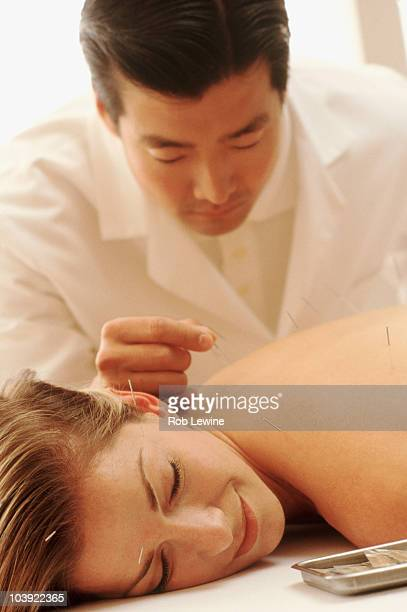 Acupuncturist putting needles in woman's back