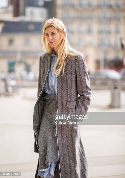 Ada Kokosar wearing a skirt worn over a stripped button shirt dress grey coat is seen outside Giambattista Valli during Paris Fashion Week Womenswear...