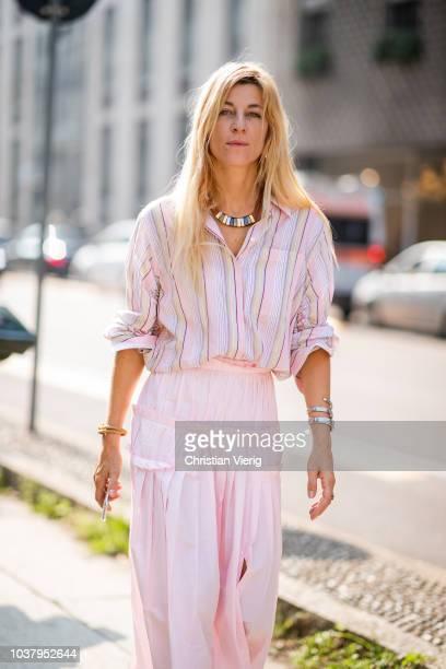 Ada Kokosar wearing pink skirt with slit pink striped button shirt is seen outside Blumarine during Milan Fashion Week Spring/Summer 2019 on...