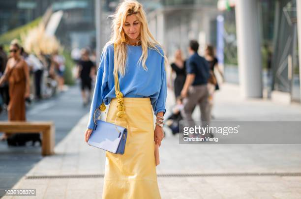 Ada Kokosar wearing yellow skirt with slit blue top and bag white ankle boots is seen outside Alberta Ferretti during Milan Fashion Week...