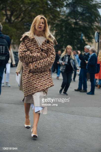 Ada Kokosar wears a light brown tweed coat and white heels at the Chanel show during Paris Fashion Week Spring/Summer 2019 on October 2 2018 in Paris...
