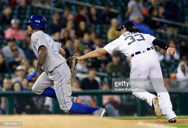 Adalberto Mondesi of the Kansas City Royals is tagged out by shortstop Pete Kozma of the Detroit Tigers after getting caught in a rundown between...