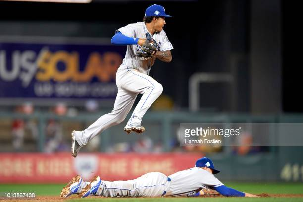 Adalberto Mondesi of the Kansas City Royals makes a play at shortstop against the Minnesota Twins as teammate Hunter Dozier dives during the game on...