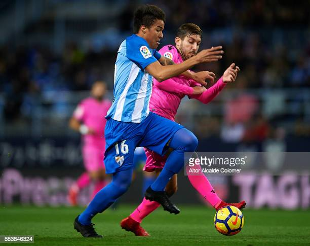 Adalberto Penaranda of Malaga CF competes for the ball with Jose Campana of Levante UD during the La Liga match between Malaga and Levante at Estadio...