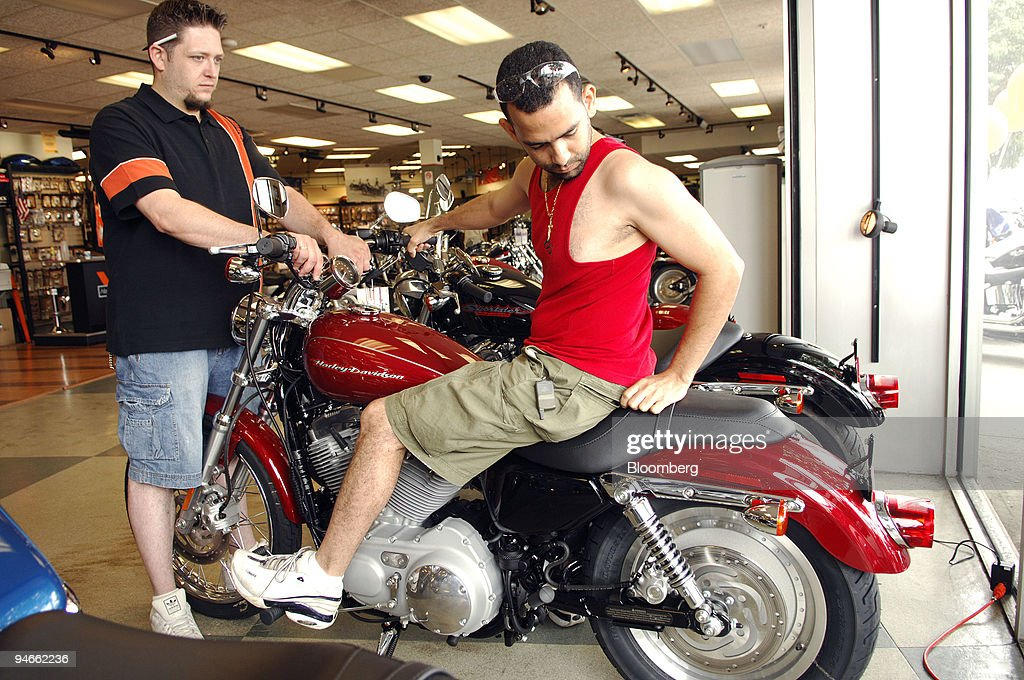 Adam Alberghine, left, supports a 2006 Harley-Davidson