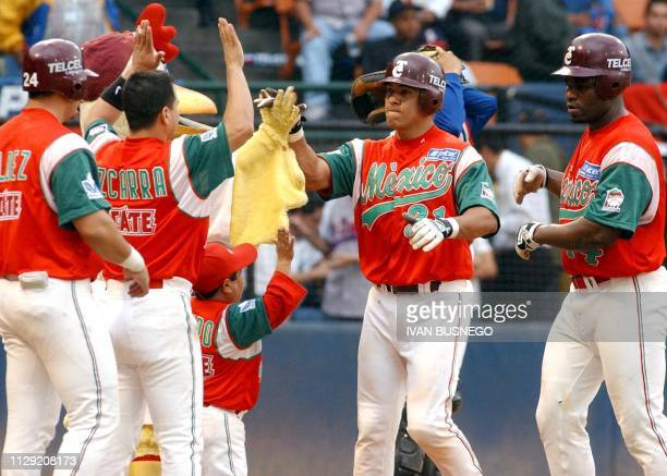 Adam Amezcua of lost Tomateros de Culiacan of Mexico is congratulated by teammates after hitting a homerun against the Tigres de Licey during the...