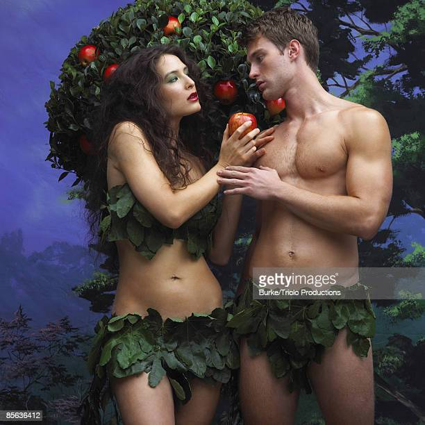 Adam and Eve holding apple near tree