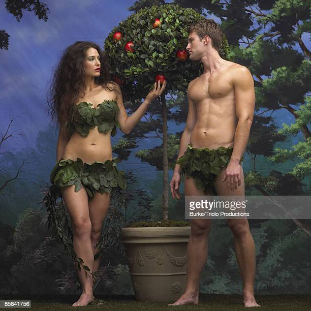 adam and eve with apple tree in garden of eden - garden of eden old testament stock photos and pictures