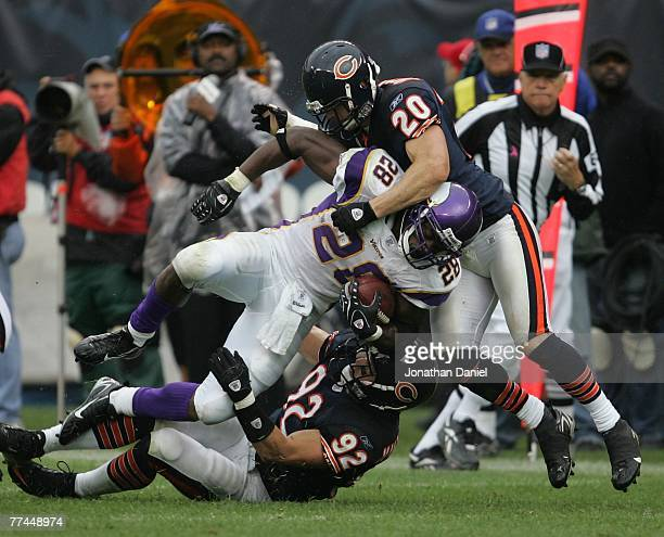 Adam Archuleta and Hunter Hillenmeyer of the Chicago Bears tackle Adrian Peterson of the Minnesota Vikings on October 14 2007 at Soldier Field in...
