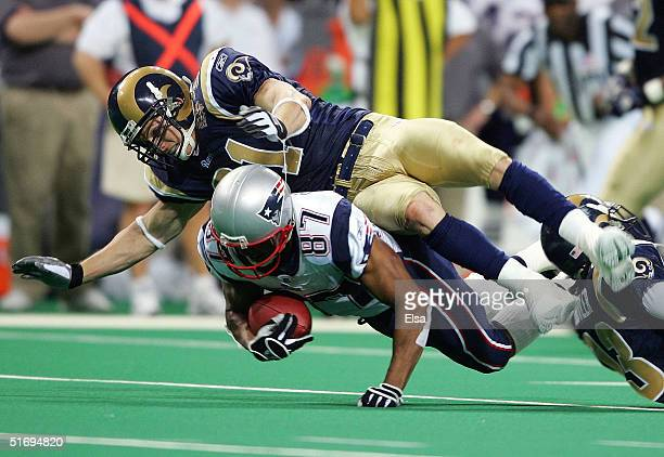 Adam Archuleta of the St Louis Rams tackles David Givens of the New England Patriots on November 7 2004 at the Edward Jones Dome in St Louis Missouri...