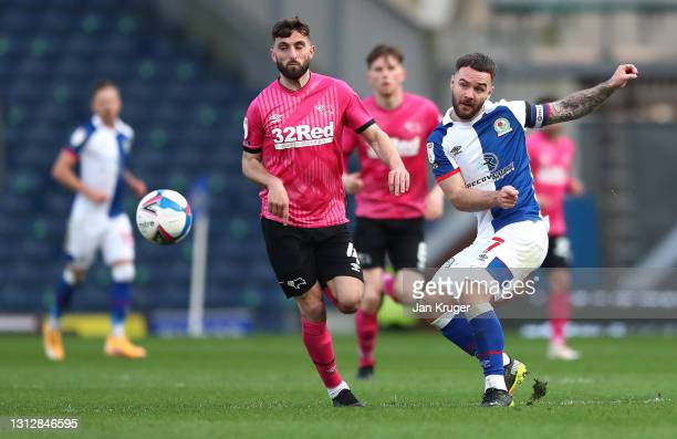 Adam Armstrong of Blackburn Rovers is challenged by Graeme Shinnie of Derby County during the Sky Bet Championship match between Blackburn Rovers and...