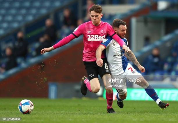 Adam Armstrong of Blackburn Rovers is tackled by Max Bird of Derby County during the Sky Bet Championship match between Blackburn Rovers and Derby...