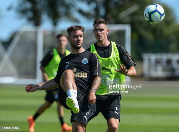 Adam Armstrong passes the ball whilst being pursued by Ciaran Clark during the Newcastle United Training Session at the Newcastle United Training...