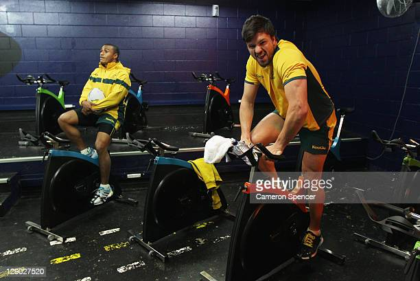 Adam AshleyCooper and Will Genia of the Wallabies work out on an exercise bike during an Australia IRB Rugby World Cup 2011 gym session at North...