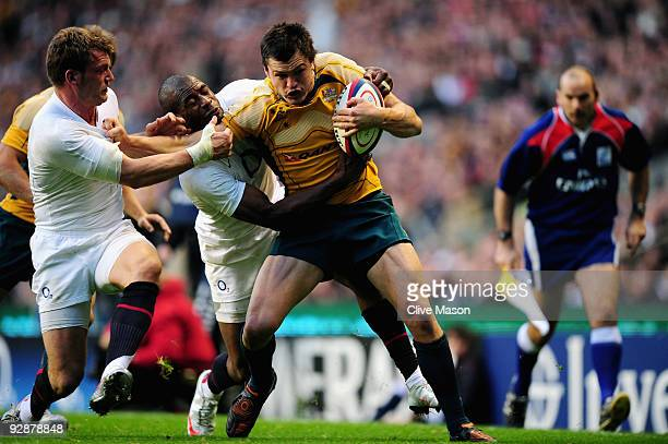 Adam AshleyCooper of Australia barges through the attempted tackles from Mark Cueto and Ugo Monye of England to score a try during the Investec...