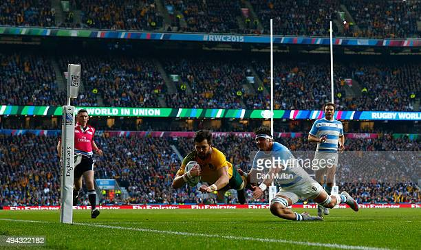 Adam AshleyCooper of Australia dives over to scores his sides second try despite the tackle by Pablo Matera of Argentina during the 2015 Rugby World...