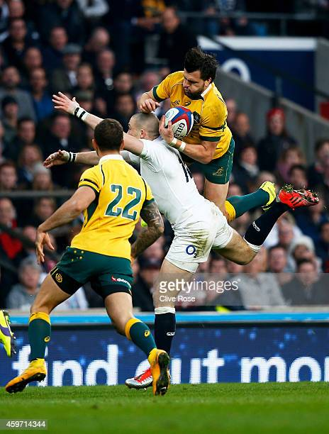 Adam AshleyCooper of Australia goes over the top of Mike Brown of England during the QBE international match between England and Australia at...