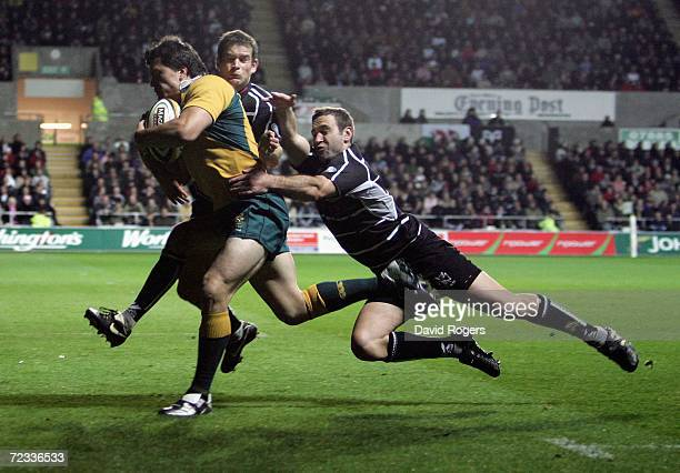 Adam AshleyCooper of Australia powers forward to score the first try despite being held by Jonathan Vaughton and Jason Spice during the rugby union...