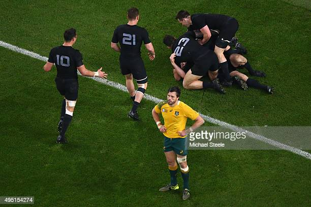 Adam AshleyCooper of Australia stands dejected as Beauden Barrett of the New Zealand All Blacks is congratulated by teammates on scoring his sides...
