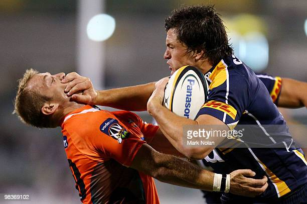 Adam AshleyCooper of the Brumbies palms off Sarel Pretorius of the Cheetahs during the round nine Super 14 match between the Brumbies and the...