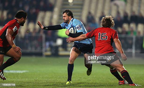 Adam AshleyCooper of the Waratahs fends Nepo Laulala with Ben Funnell of the Crusaders in defence during the round 16 Super Rugby match between the...